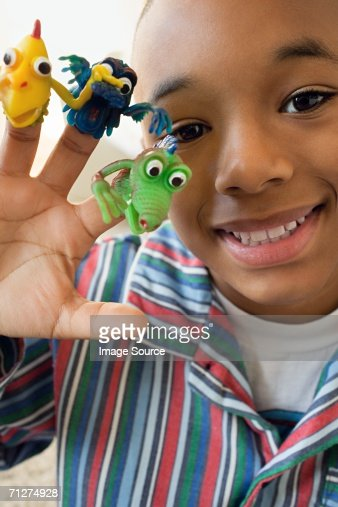 Boy indoors with monster finger puppets on fingers