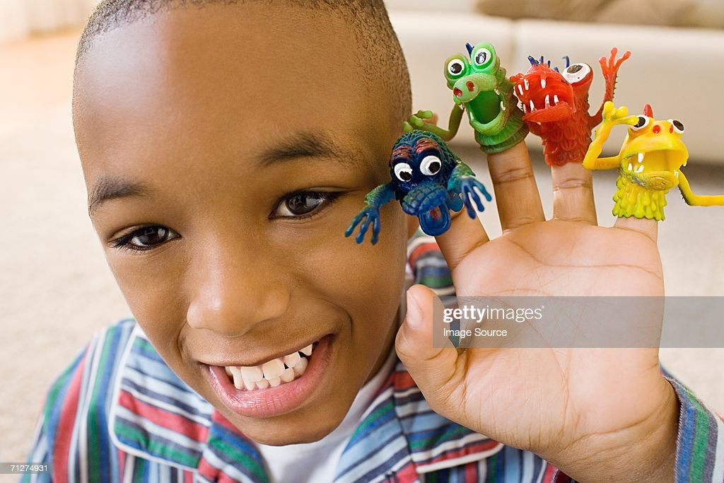 Boy indoors with monster finger puppets on fingers : Stock Photo