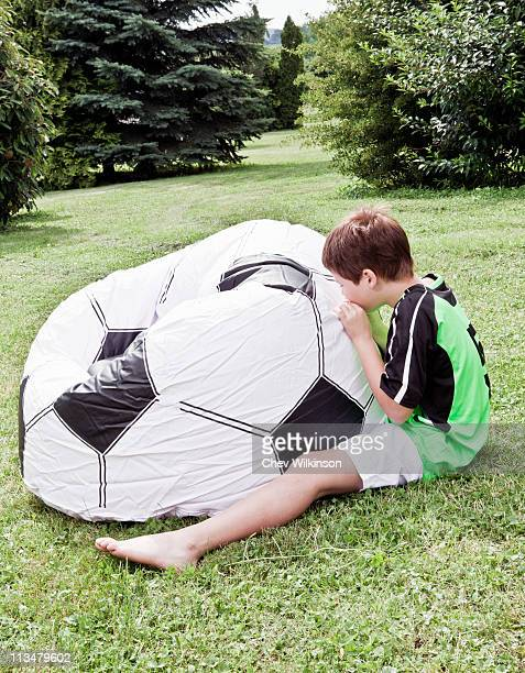Boy inflating giant football