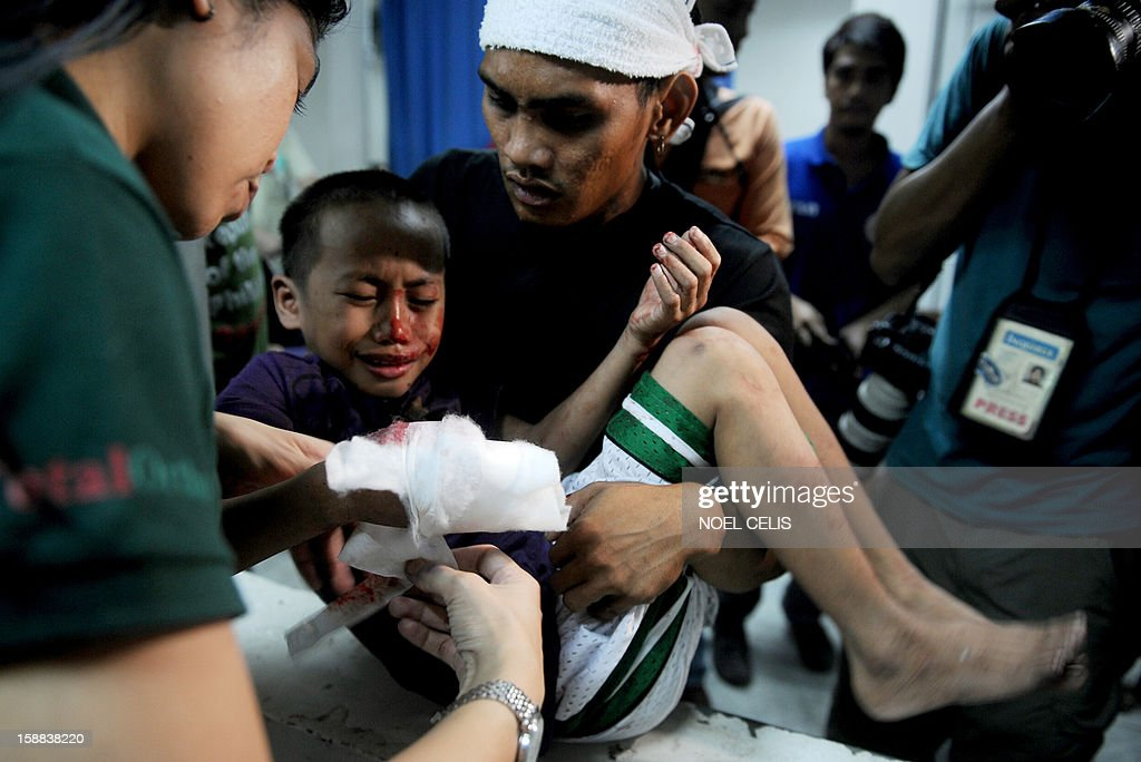 A boy injured by a firecracker arrives at the Jose Reyes Memorial Medical Center in Manila early on January 1, 2013, after new year's celebrations. The Philippines is mainly Roman Catholic but the celebrations draw on ancient superstitions and Chinese traditions in which the noise from firecrackers is meant to drive away evil spirits and bring good luck in the coming year. Adding to the danger of annual fireworks celebrations in the streets, there are over 1.2 million unlicensed firearms in the Philippines and some of those are used in the festivities.