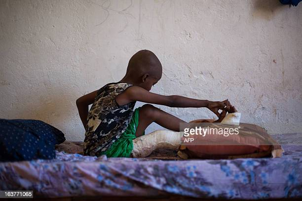 A boy injured with a broken leg sits on a bed at Kismayo General Hospital in the portcity of Kismayo 500km south of Somalia's capital on March 15...