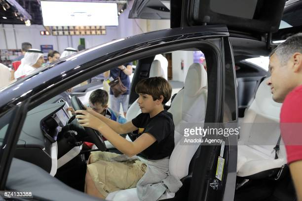 A boy inspects the X of Tesla during Dubai International Motor Show 2017 at Dubai World Trade Centre in Dubai United Arab Emirates on November 14 2017