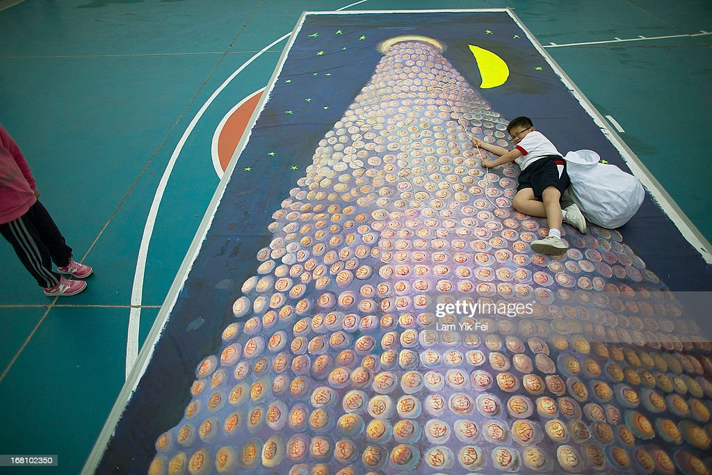 A boy interacts with a 3D painting at the selection contest for the finalists of the Cheung Chau Bun Scrambling Competition in Cheung Chau, Hong Kong. The Cheung Chau Bun scrambling Competition is a part of Tai Ping Qing Jiao Festival. the Purest Sacrifice celebrated for Great Peace and the day of festivitie ends with guests climbing 20-metre bamboo towers to retrieve 'lucky' buns dotted up their length.