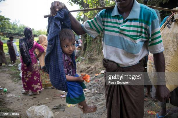 A boy is carried by his father in a new wave of Rohingya arrivals walking across the border from Myanmar September 24 2017 in Thainkhali Cox's Bazar...