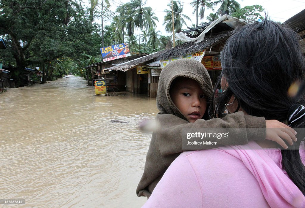 A boy is carried by his mother after heavy rains and strong winds, brought about by Typhoon Bopha, hit the township of Mabini on December 04, 2012 in the province of Compostela Valley in the southern Philippines. Typhoon Bopha made landfall in the southern Philippines earlier today, bringing heavy rain and wind gusts of 210 km/h (130mph). So far at least 40 have died and over 40,000 people have been forced into shelters.