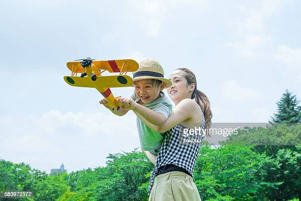 Boy is facing a mother playing with airplane