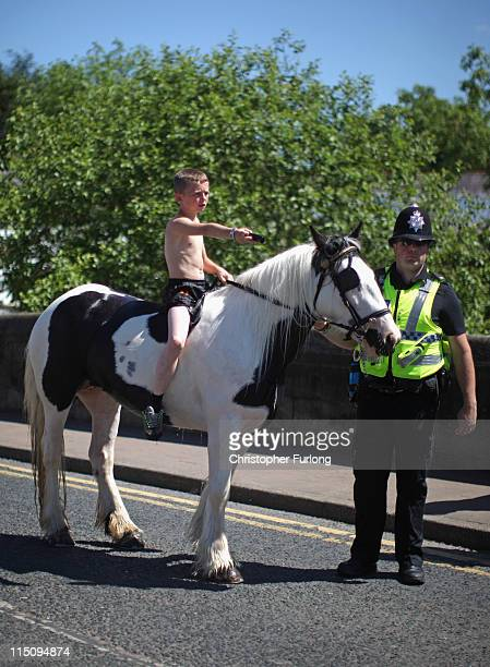A boy is given a helping hand by a policeman as he rides his horse down the street at the Appleby Horse Fair on June 3 2011 in Appleby England...