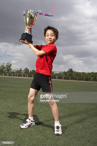 A boy is holding the trophy.