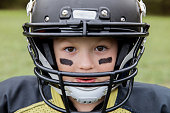 Little league American football player is staring into camera. Caucasian elementary age little boy is wearing a helmet and protective pads under a football team jersey, and has black face paint below