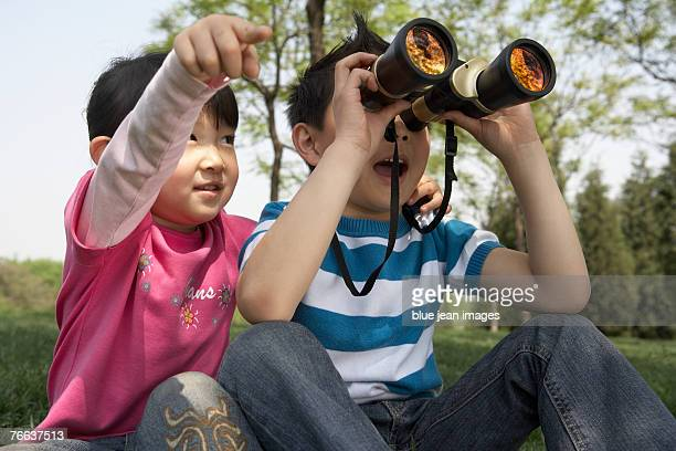 A boy is looking through binoculars.