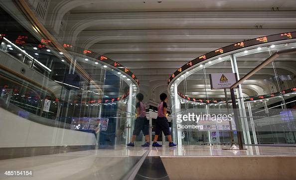 A boy is reflected in glass while walking through the Tokyo Stock Exchange operated by Japan Exchange Group Inc in Tokyo Japan on Tuesday Aug 25 2015...