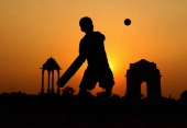 A boy is seen playing cricket against a setting sun at India Gate on October 26 2011 in Delhi India