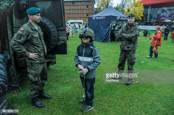 A boy is seen trying on a Kevlar helmet with night vision goggles on NATO day in Bydgoszcz Poland on October 14 2017