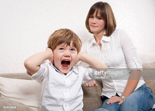 Boy is shouting and mother looks angry