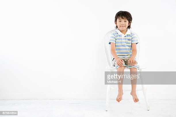 A boy is sitting on white chair in front of wall