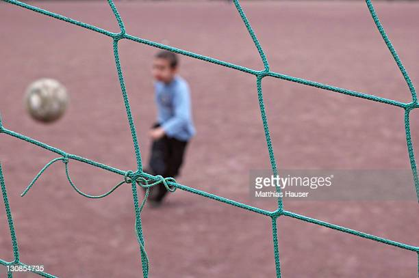 A boy is trying to make a goal