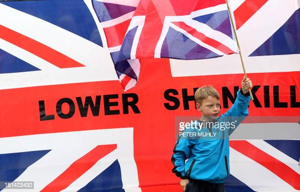 A boy joins loyalist protesters in waving the British Union Flag ahead of a loyalist march to Woodvale Parade in Belfast Northern Ireland on...