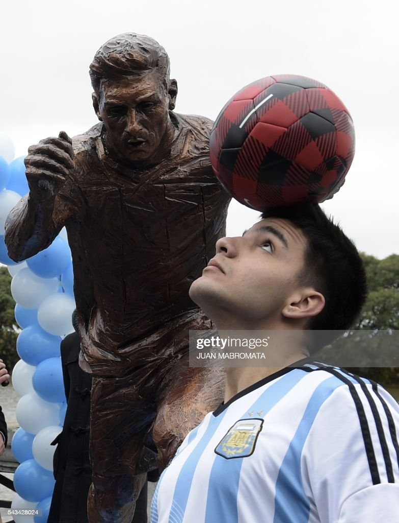 A boy juggles with a football after a sculpture of Argentina's forward Lionel Messi was unveiled by Buenos Aires Mayor Horacio Rodriguez Larreta at the Paseo de la Gloria which pays tribute to Argentine renowned sports figures, in the South Coast promenade in Buenos Aires, on June 28, 2016. / AFP / JUAN