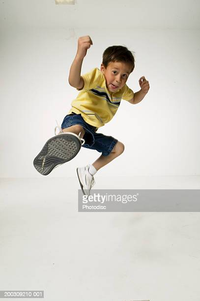 Boy (8-9), jumping and kicking in studio, portrait