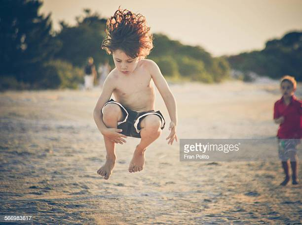 Boy jumping at the beach.