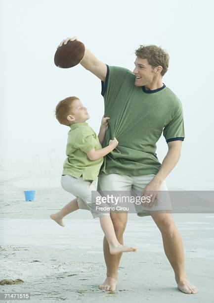 Boy jumping for ball in father's hand, on beach