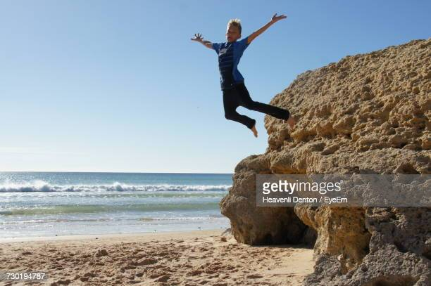 Boy Jumping From Rock Formation On Shore At Beach Against Sky