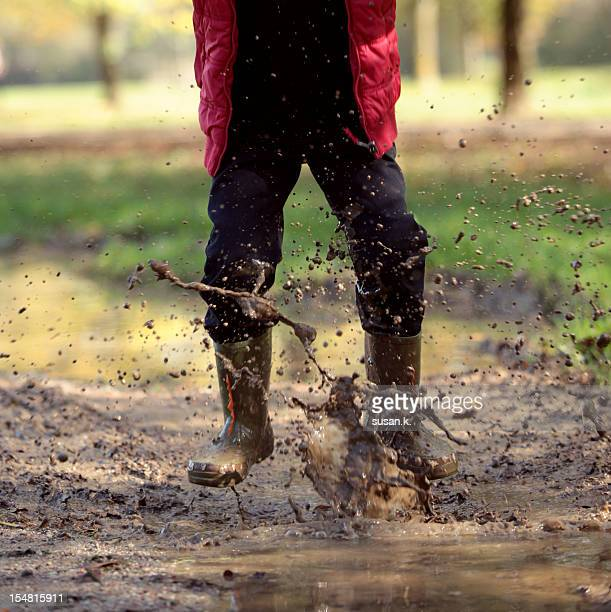 Boy jumping in a pool of mud.