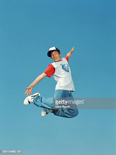 Boy (12-14) jumping in air, arms outreached, low angle, portrait