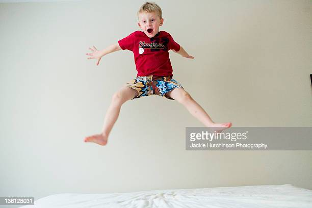 Boy jumping in air on bed