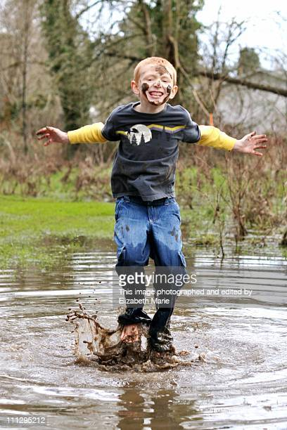 Boy jumping in huge muddy puddle