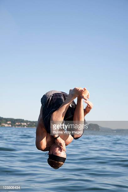 Boy jumping in lake from a boat