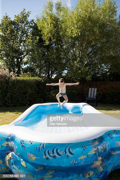 Boy (4-6) jumping in large  paddling pool