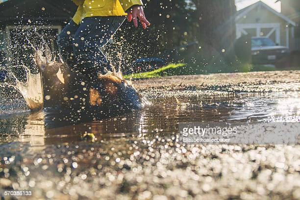 Boy jumping in puddle of muddy water