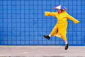 Boy jumping in raincoat and umbrella hat