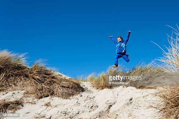 Boy jumping in sand