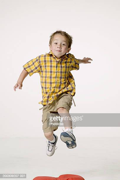 Boy (8-9), jumping in studio, portrait