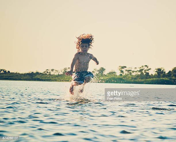 Boy jumping in the water at the bay.