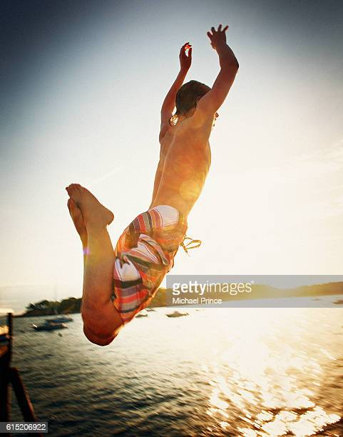 Boy jumping in to lake
