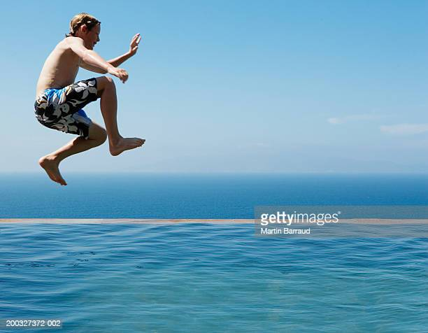 Boy (9-11) jumping into infinity pool