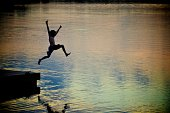 An unidentifiable boy joyfully leaps into a lake at sunset.