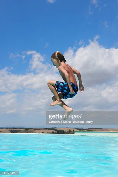 Boy jumping into swimming pool, Buonconvento, Tuscany, Italy