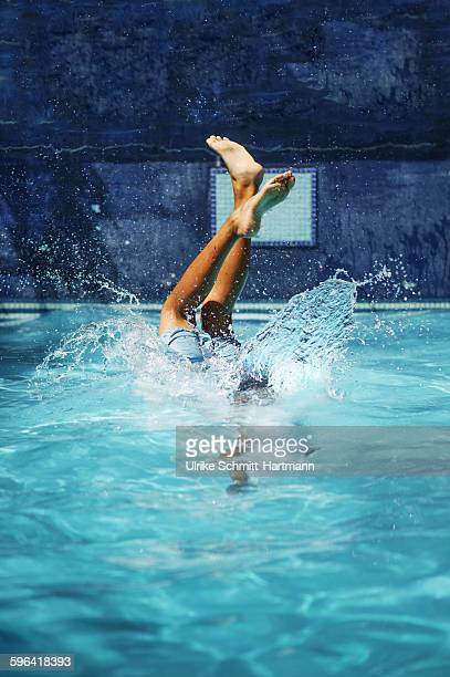 Boy  jumping into swimming pool on a sunny day