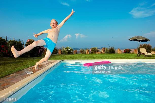 Petit garçon sauter dans la piscine