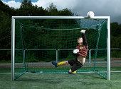 Boy (8-9 years) jumping mid air catching ball at goal post