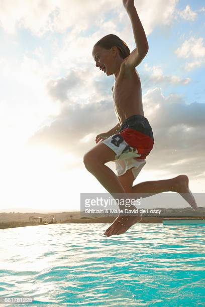Boy jumping mid air into swimming pool, Buonconvento, Tuscany, Italy