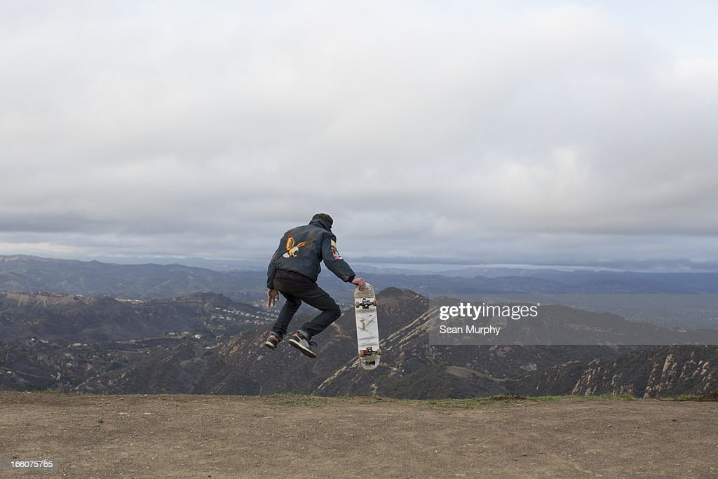 boy jumping of hill with skateboard : Stock Photo