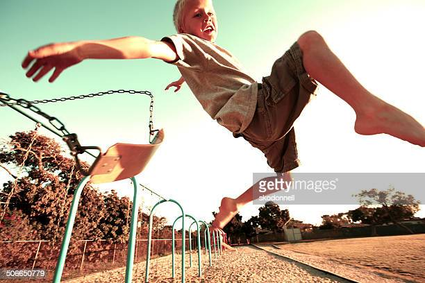 Boy Jumping off a Swing