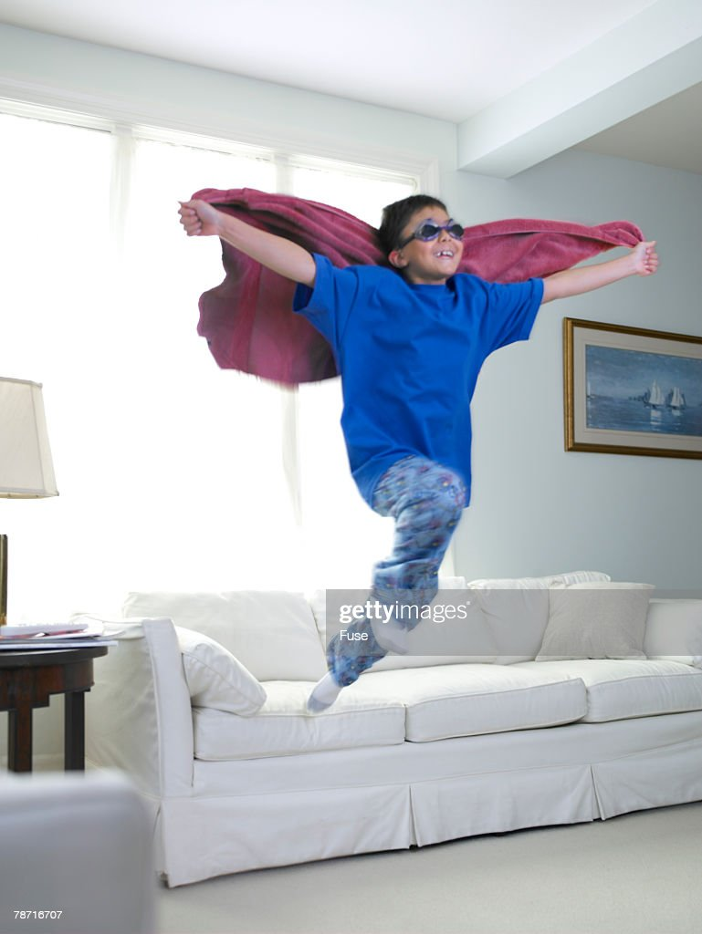 Boy Jumping Off Couch Playing Superhero Stock Photo
