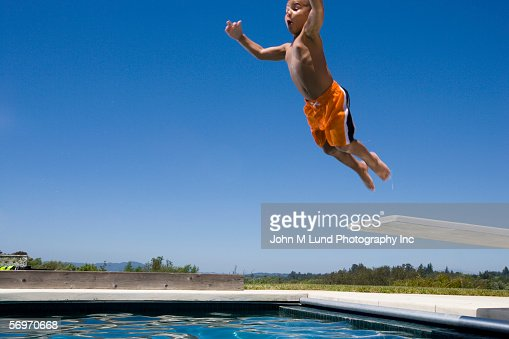 Boy Jumping Off Diving Board Into Swimming Pool Stock Photo Getty Images