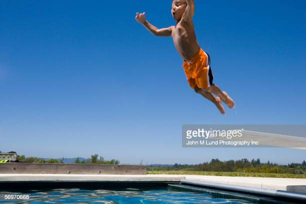Boy jumping off diving board into swimming pool